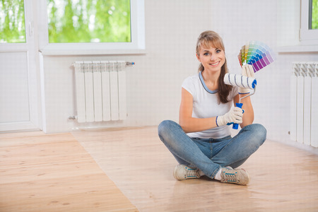 paintroller: beautiful smiling female worker sitting on wooden floor and showing paintroller and color palette