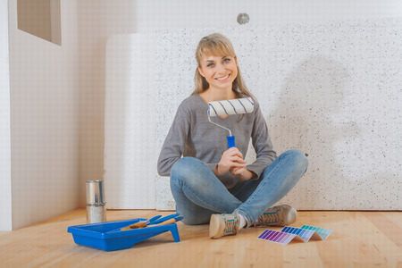 paintroller: happy smiling female painter sitting on wooden floor and holding paintroller