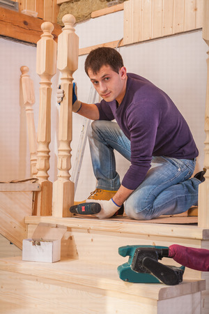 young worker fixing post of wooden  ladder and looking at camera photo