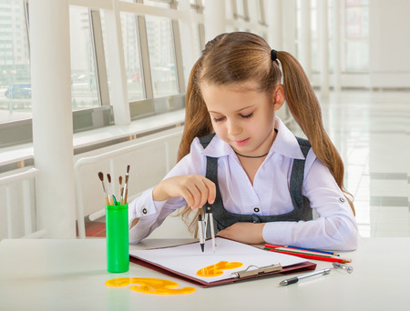litle: beautiful litle schoolgirl siiting at table and drawing with compass Stock Photo