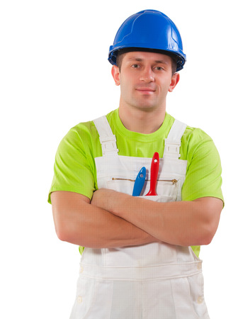 a men wearing working clothes with paint brushes in pocket and crossed arms looking at camera   isolated photo