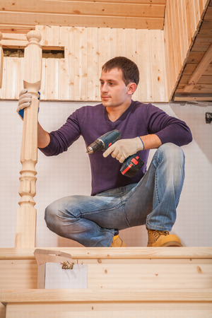 a young worker sitting and holding cordless drill photo