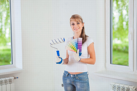 paintroller: smiling female holding paintroller and color palette at home Stock Photo