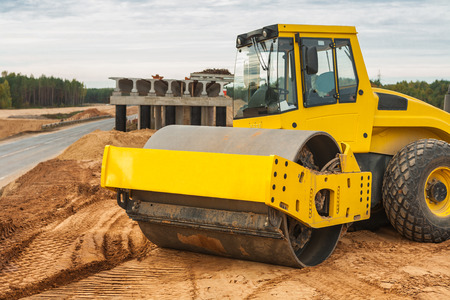 construction vibroroller: sand compactor on pile of sand Stock Photo