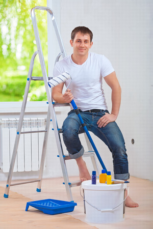 a young painter sitting on stepladder and holding paintroller
