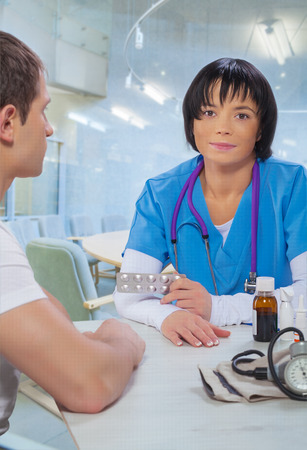 asian female doctor with patient sitting at table and speaking photo