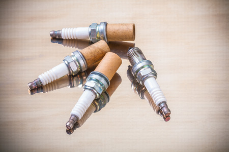 sparking plug: old sparks plugs on light brown background Stock Photo