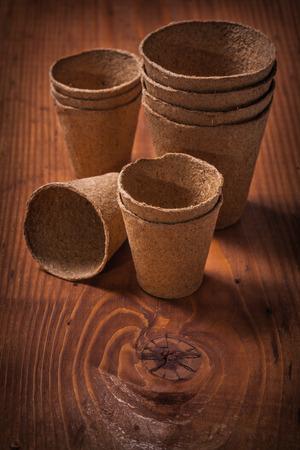 turba: macetas de turba sobre tabla de madera