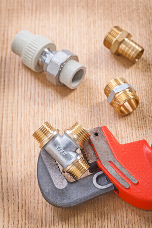 household fixture: plumber fixtures and wrench on wooden board