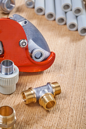 household fixture: plumbing fixtures and pipe cutter with pipes on wooden board Stock Photo