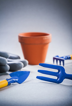 small group of objects: small garden tools on gray background