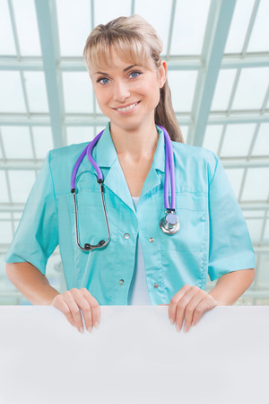 beautyful toothy smiling female doctor with white placard photo