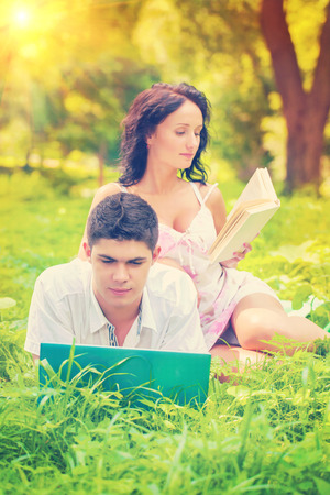 resting couple with laptop and book in park on grass photo