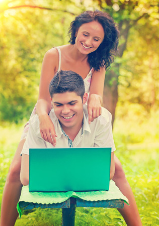 copule: un joven Copule feliz sonriente con la computadora port�til en el parque