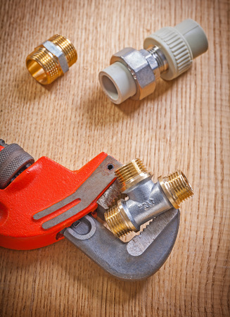 pipe fixtures and monkey wrench on wooden board close up photo