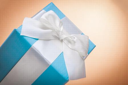 mo�o blanco: caja de regalo con lazo blanco sobre backgrond de color marr�n claro con copyspace