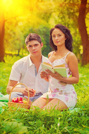 beautiful couple resting on grass in evening photo