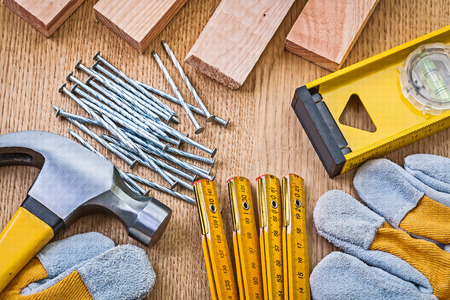 home improvement: gloves hammer level nails planks on wooden board