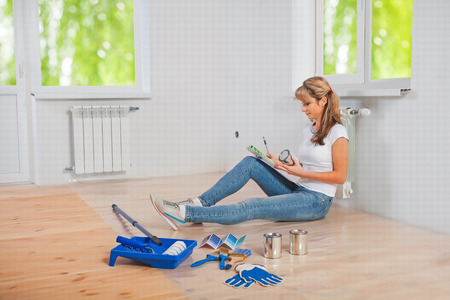 home improvement: young female painter sitting on the floor holding color palette and looking on it