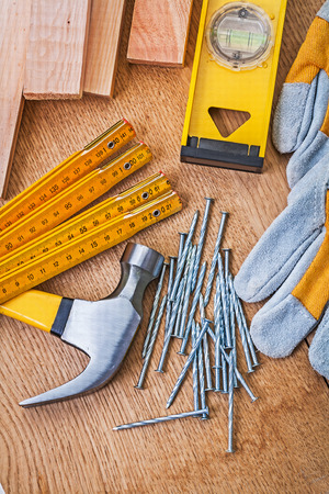 carpentry tools nails claw hammer protective gloves level planks on wooden board photo