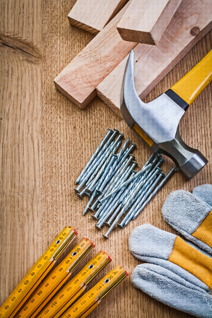 composition of carpentry tools nails wooden meter protective glove claw hammer planks on wooden board photo