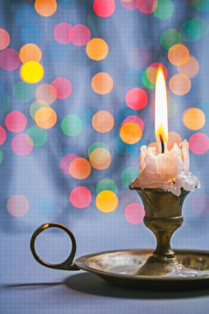 copyspace image vintage candlestick with burning candle on background of abstract bokeh Stock Photo