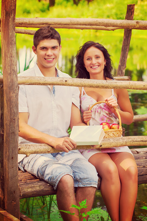 beautiful smiling couple sitting on old wooden bridge on small river    photo