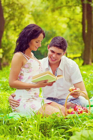 young female and male sitting on grass smiling and writing the book   photo