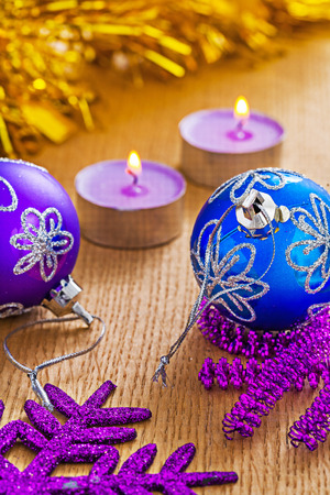 christmas baubles and glowing candles on wooden boards photo