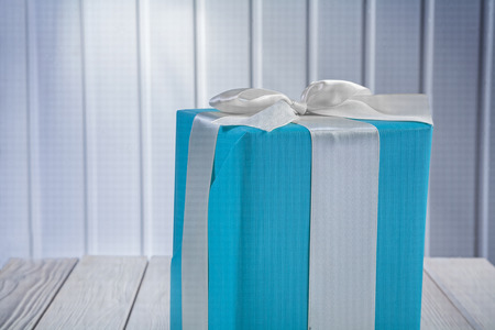 blue gift box: close up view on blue gift box with white ribbon on wooden board