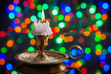 multycolored: glowing old candle in wintage candlestick on surface of mirror with multycolored bokeh horizontal version Stock Photo