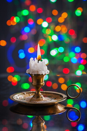 multycolored: glowing old candle in wintage candlestick on surface of mirror with multycolored bokeh