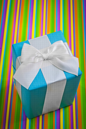 blue gift box: classical blue gift box with white bow on colored striped background