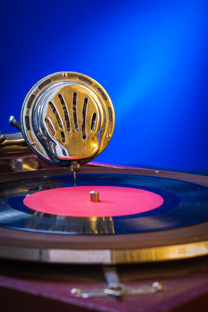 Old gramophone on blue background very close up photo
