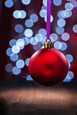 multycolored: Red christmas ball hanging on a pink ribbon on a wooden table and blurred bokeh background