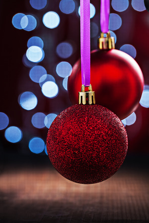multycolored: two red christmas balls hanging on pink tape on old wooden table and blurred bokeh background Stock Photo