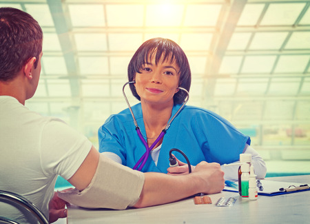 beautiful asian female doctor sitting at the table with patient measuring blood pressure smiling and looking at camera   photo