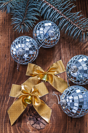 golden bows and christmas disco balls with pinetree branch on old wooden board photo