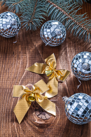 golden christmas bows and mirror disco balls with pinetree branch on old wooden board photo