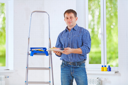 handsome young homeowner holding color palette and looking at camera photo
