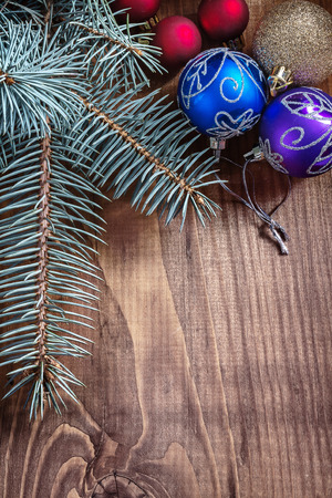 multycolored christmas balls with pinetree branch on old wooden board close up