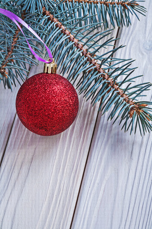 kerstbal rood: mat red christmas ball and pinetree branch on white wooden board Stockfoto