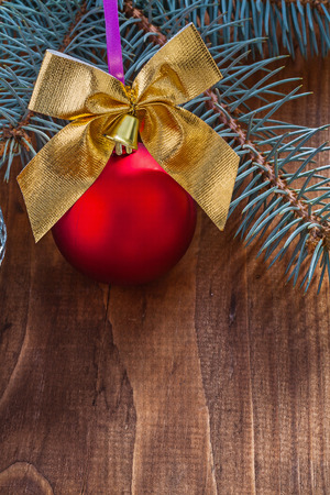 pine tree branch: red christmas bauble and gold colored bow with small bell on old wooden board with pine tree branch