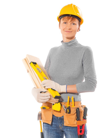 caucasianf female worker with construction tools holding wooden planks and level isolated on white photo