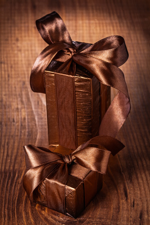 two brown giftboxes with bows on old wooden brown board photo