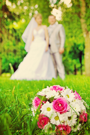 verry: wedding bouquet on green grass and verry blurred young wedding couple stile