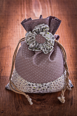 ornated: small ornated bag with strings on old wooden board