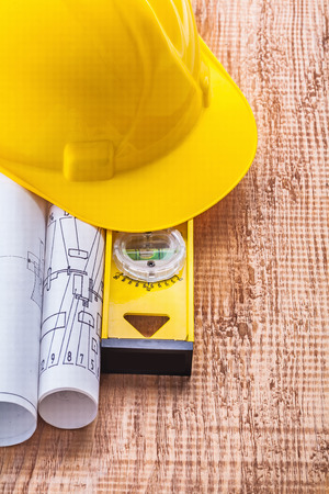 construction level: yellow hardhat white blueprints and construction level on old wo Stock Photo