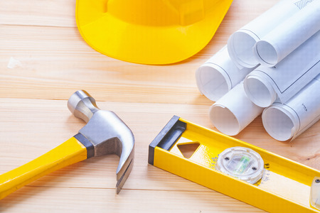 construction level: claw hammer rolled blueprints construction level hardhat on wood Stock Photo