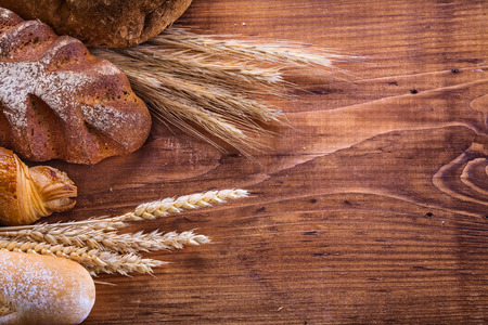 bakery products: composition of breads and wheat ears on old wooden boards